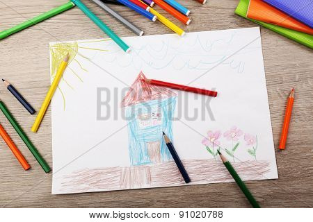 Kids drawing on white sheet of paper with crayons and markers on wooden table, closeup