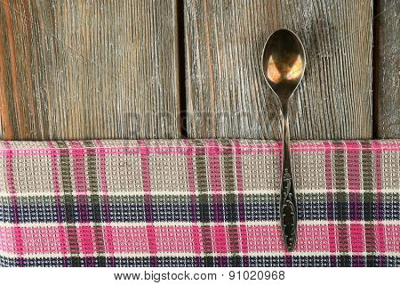 Checkered napkin with spoon on wooden table background