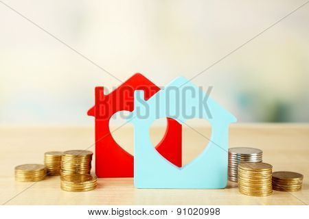 Model of houses with coins on bright background