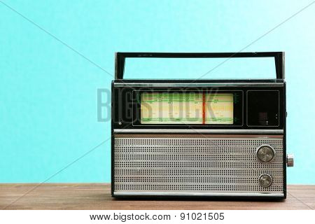 Old retro radio on table on green wall background