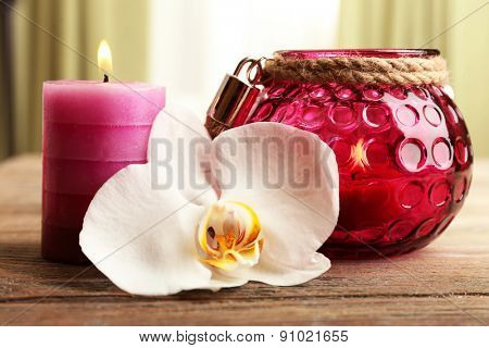 Spa still life with candle and white orchid flower on wooden table on light background