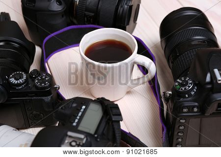 Modern cameras with cup of coffee on wooden table, closeup