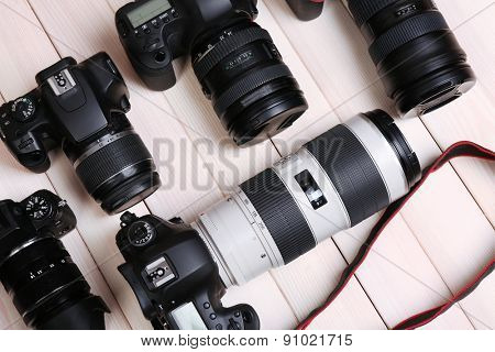 Modern cameras on wooden table, closeup
