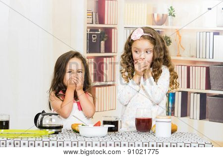 Two young preschooler girls covering their mouths refusing to eat