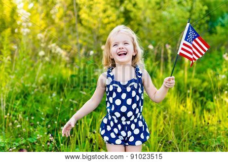 Laughing Blond Little Girl With Long Curly Hair Holding American Flag And Waving It