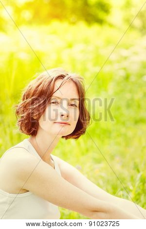 Outdoor Portrait Of Adorable Freckled Young Woman Who Sitting On Green Grass In Summer Sunny Park