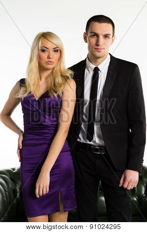 Man and woman posing on a white background. Unhappy girl turned away from the guy.
