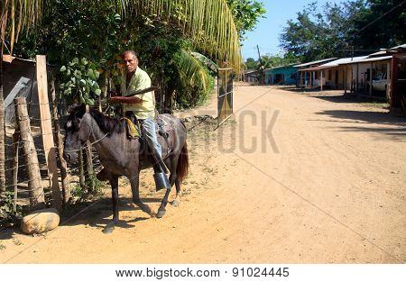 A Man Riding A Horse With Machete In Rural Honduras