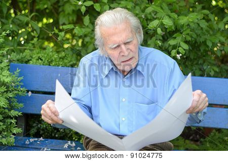 Elderly Man Sitting Alone On A Bench In The Park