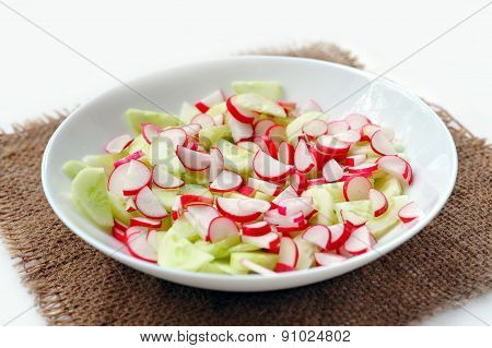 Fresh salad in plate at sackcloth on white background. Not isolated