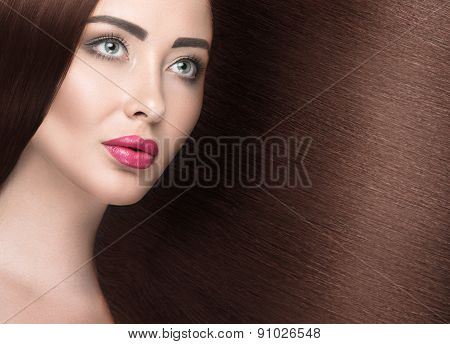 Beautiful brunette girl with a perfectly smooth hair and classic make-up. Beauty face.