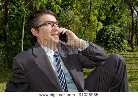 Happy businessman outdoor talking through mobile phone