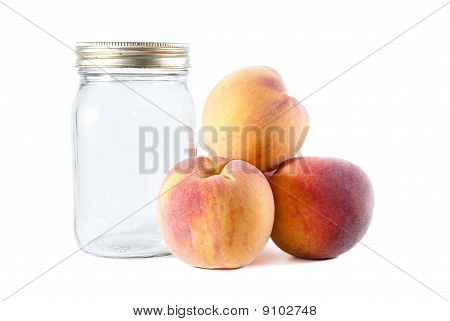 Canning Ripe Peaches Beside A Glass Jar On Isolated Background