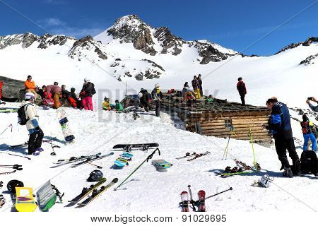 Val Thorens Alps France March 18 2014: Skiers and snowboarders are resting around old wooden hut