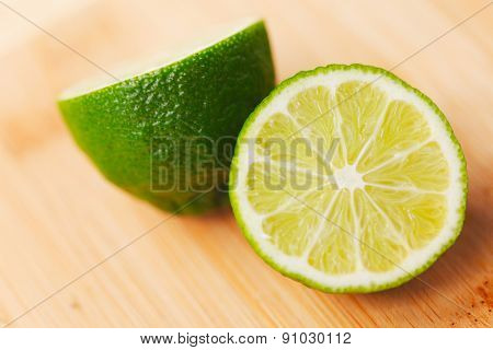 Cut lime on a wooden board close-up