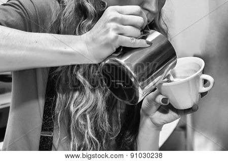 Female bartender in the workplace. Girl makes coffee using coffee machine.