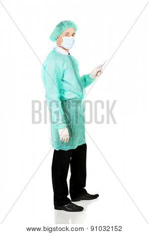 Full length side view male doctor with a scalpel.