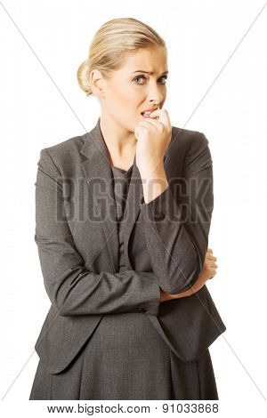 Stressed young woman biting her nails.
