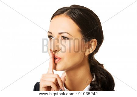 Portrait of businesswoman making silent sign.