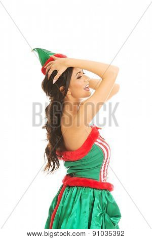 Side view of woman wearing elf clothes, touching her head.