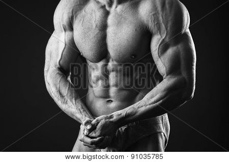 Young bodybuilder guy in good shape against a dark background.