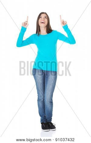 Full length happy woman pointing up.