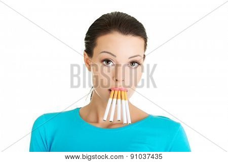 Young woman with group of cigarettes in mouth.