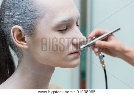 The process of putting airbrush make up. The process of changing the color of the hair and skin.
