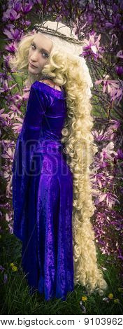 Young woman dressed like Rapunzel with long blond hair.