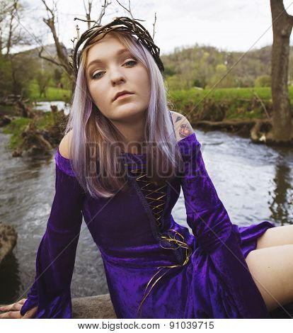 Young woman in purple gown sitting by a river