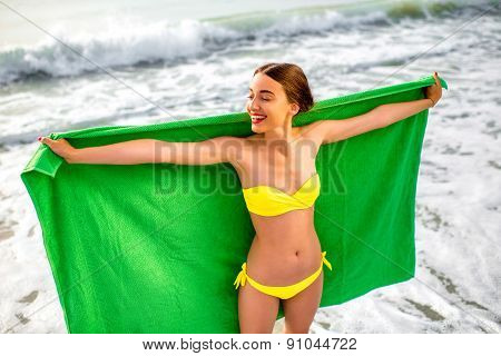 Woman in green towel on the beach