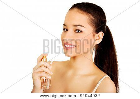 Young beautiful woman applying parfume.