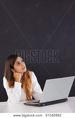 Woman thinking next to a blackboard