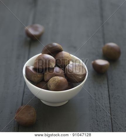 Whole chestnuts in a white bowl on dark background.