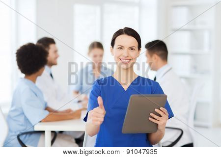 clinic, profession, people and medicine concept - happy female doctor with tablet pc computer over group of medics meeting at hospital showing thumbs up gesture