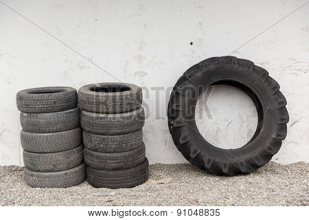 tire, maintenance, service and motor transport concept - close up of wheel tyres stored near wall