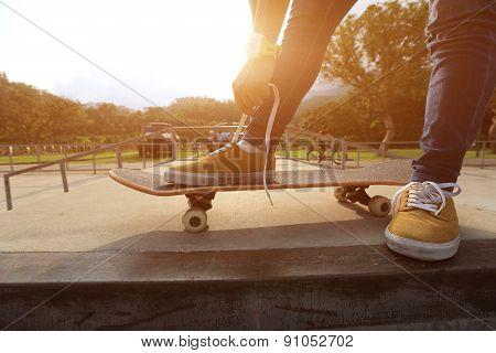 skateboader hands tying shoelace on skateboard