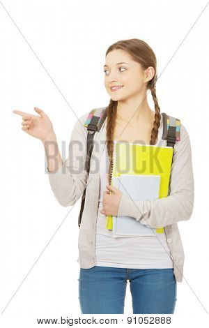 Teenager girl with school backpack pointing aside.