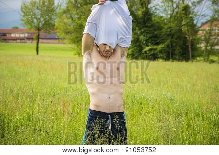 Handsome fit young man at countryside, undressing