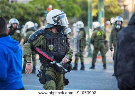 ATHENS, GREECE - CIRCA APR, 2015: Riot police with their shield, take cover during a rally in front of Athens University, which is under occupation by protesters leftist and anarchist groups.