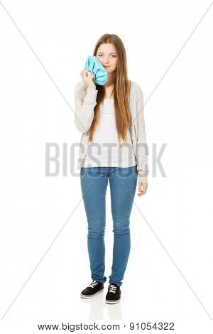 Teen woman with toothache and ice bag.