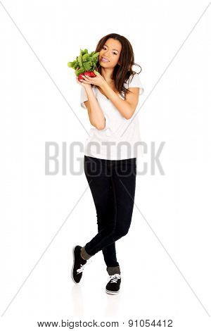 Young african woman with bunch of radishes.