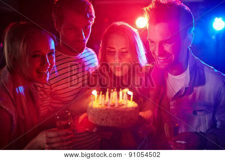 Young girl blowing candles on birthday cake between her friends