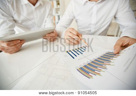 Hand of businessman with pencil pointing at data in document