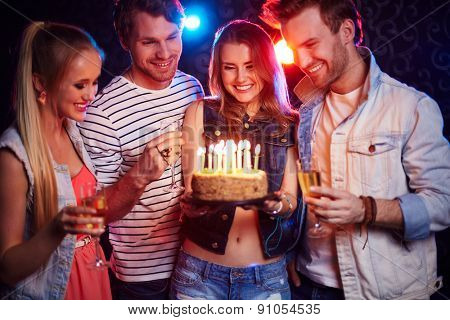 Two young couples with champagne and cake looking at candles at birthday party