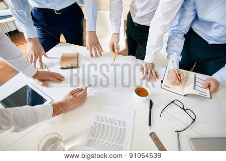 Group of architects discussing sketch of building