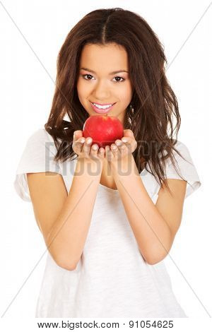 Beautiful young african woman holding an apple.