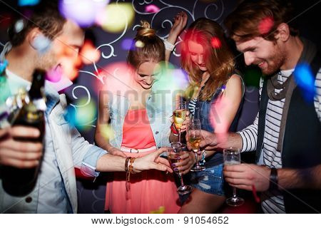 Group of young friends with flutes of champagne having party in club
