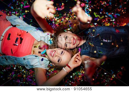 Two energetic girls with raised arms looking at camera in nightclub
