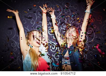 Two energetic girls dancing with raised arms